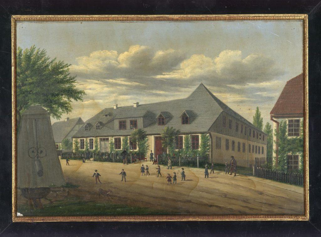 Im Bildzentrum befindet sich die Kleinwelkaer Knabenanstalt, ein schlichter einstöckiger Bau. Auf dem Platz vor dem Schulgebäude sind etliche spielende Kinder mit ihren Erziehern zu sehen. Den linken Bildrand dominiert ein hölzernes Brunnhaus.