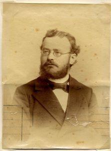 Porträt von Arnošt Muka. Mittelalter M;ann mit Brille, dunklem Haar und dunklem Bart. Er trägt eine dunkle Jacke und eine Fliege.